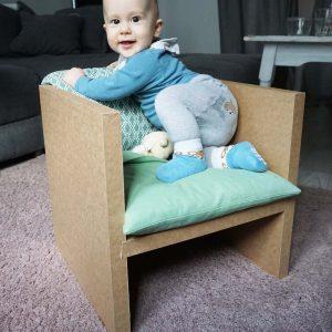 Baby sitzt auf Papphocker
