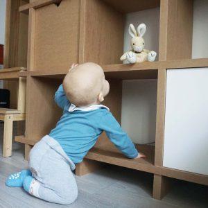 Baby klettert auf Pappregal