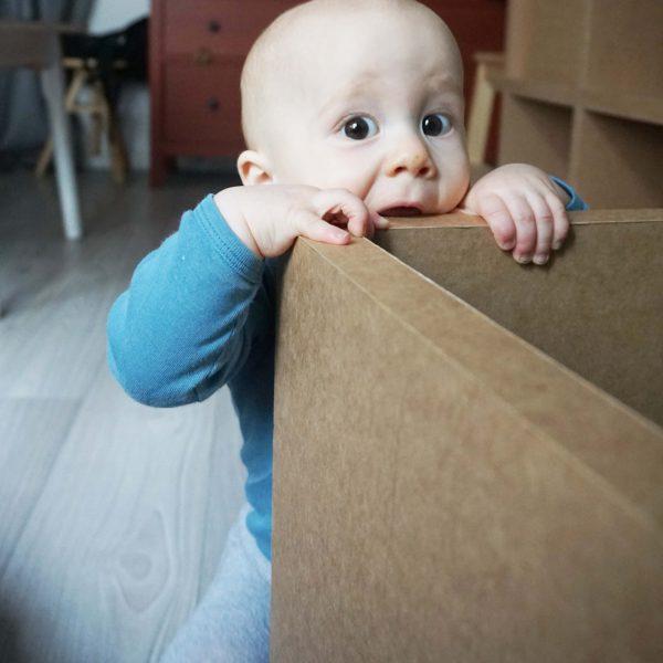 Papiermöbel Baby klettert auf Papphocker